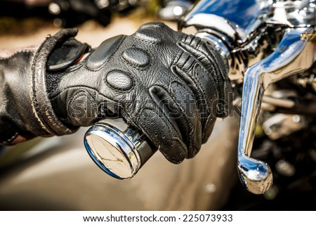 Human hand in a Motorcycle Racing Gloves holds a motorcycle throttle control. Hand protection from falls and accidents. - stock photo