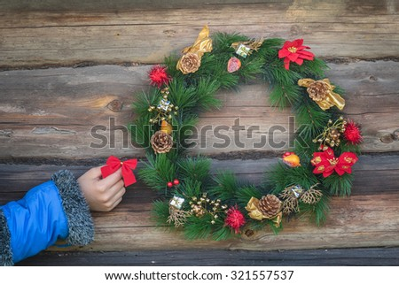 Human hand is holding red bow and hanging on rustic log cabin wall with Christmas wreath - stock photo