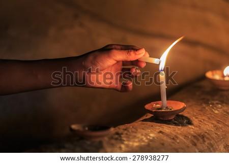 human hand lighting the candle - stock photo