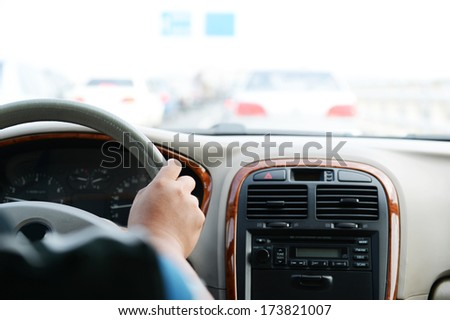 Human hand on steering wheel inside of a car. - stock photo