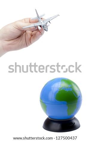 Human hand playing Miniature military jet landing on the globe - stock photo