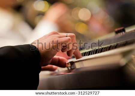 Human hand playing the synth at the concert - stock photo
