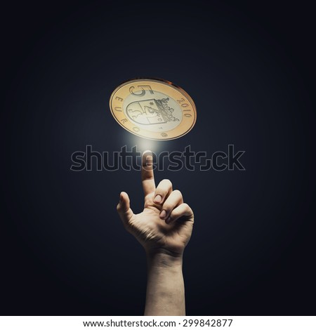 Human hand pointing with finger at euro coin - stock photo