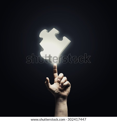 Human hand pointing with finger at puzzle element - stock photo