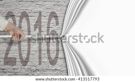 Human hand pulling blank white curtain covered 2016 on old brick wall background - stock photo