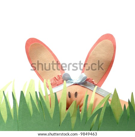 Human hand puppet dressed as the Easter bunny hiding behind paper grass over a white background - stock photo