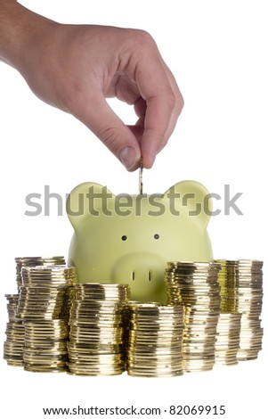 Human hand putting a golden coin into a green piggy bank that is surrounded by stacks of golden coins on a white background. - stock photo