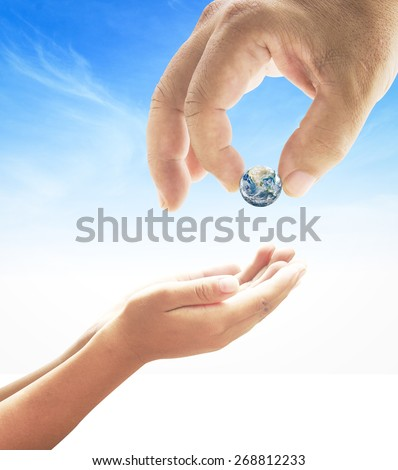 Human hand sending the earth into another hands on beautiful blue sky background. environment concept. Elements of this image furnished by NASA. - stock photo