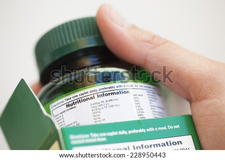 Human hand take out bottle with vitamin pills from the box for reading Nutritional information. - stock photo