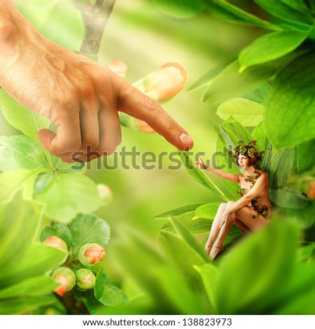 Human hand touching his finger to finger of garden fairy sitting on a green plant - stock photo