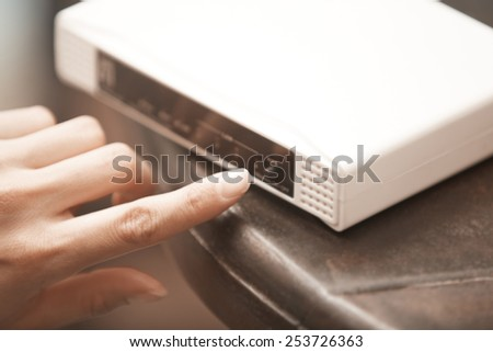 Human hand turning on wireless modem. Close-up horizontal photo - stock photo