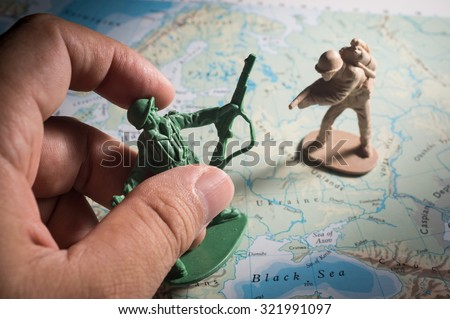 Human hand with soldier toys on map,war concept.. - stock photo