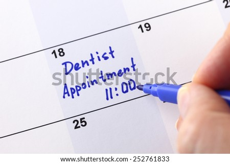 """Human hand writes reminder """"Dentist appointment 11:00"""" in calendar. - stock photo"""