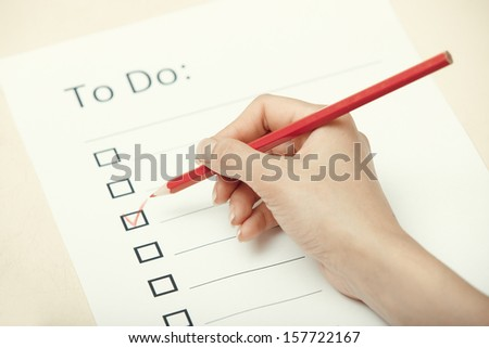 Human hand writing on a checklist document - stock photo