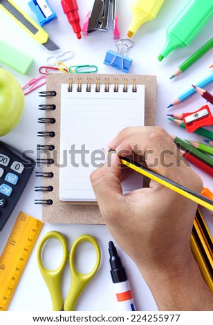 Human hand writing on blank small notebook with school stationery on white background.  - stock photo