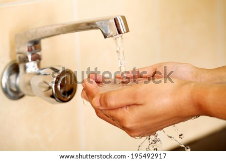 Human hands being washed under stream of pure tap water  - stock photo