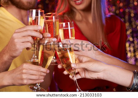 Human hands cheering up with champagne at party - stock photo