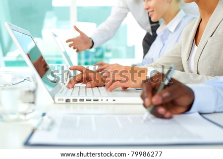 Human hands during paperwork and typing in office - stock photo