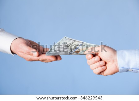Human hands exchanging money on blue background, closeup shot - stock photo