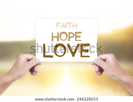 Human hands holding a handwritten text for FAITH, HOPE, LOVE over blurred nature background. Encouraging Evangelism Biblical Religion Peace Spiritual Church Gospel Christian God Trust concept. - stock photo