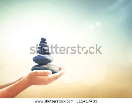 Human hands holding balanced seven Zen stones over blurred beautiful nature background. Ecology, Sustainability, World Mental Health Day, Philosophy, Investment, Insurance, Balancing, Business concept - stock photo