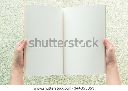Human hands holding blank open book, catalog, magazines, brochure, note template with paper texture on blur light cream color carpet floor background: Empty textured note book pages from top view  - stock photo