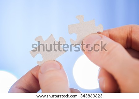 Human hands holding details of puzzle, blue background - stock photo