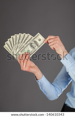 Human hands holding fan of dollars, closeup shot on dark background - stock photo