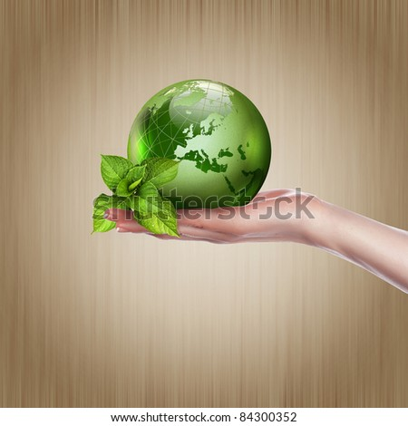 human hands holding green earth with a growing plant - stock photo