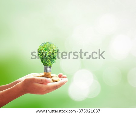 Human hands holding lightbulb of tree on golden coins over blurred nature background. Ecology, World Thinking Day, Eco Friendly, Spring, Environment, Go Green, Saving, Technology concept. - stock photo