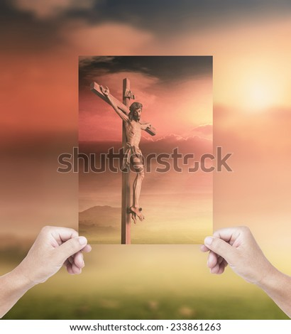 Human hands holding picture Jesus christ on the cross over a sunset background compare with the actual location. - stock photo