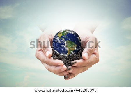 Human hands holding soil emerges from the sky in the background blurred. Create a new world. loves the world.Environment Day concept.Ecology concept. Elements of this image furnished by NASA. - stock photo