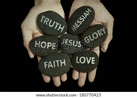 Human hands holding stones with religion text - stock photo