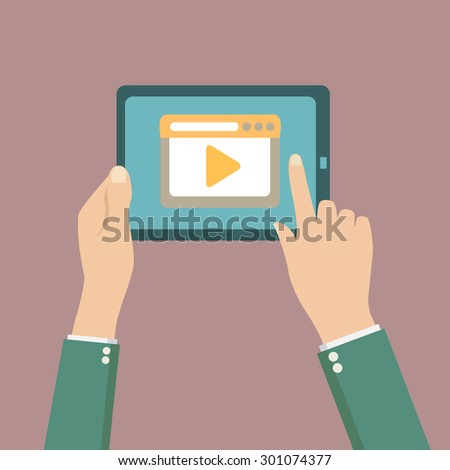 Human hands holding tablet computer with video player on the screen - stock photo