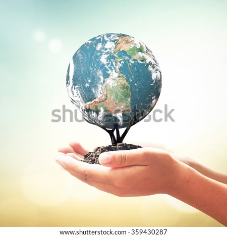 Human hands holding tree of planet over blurred beautiful sunset background. Ecology, World Environment Day, Investment, CSR, Health Care, Healthcare concept. Elements of this image furnished by NASA - stock photo