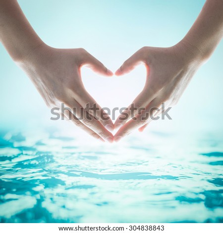 Human hands in heart shape showing love and friendship on blurred wavy clean water background: Saving and monitoring water and natural environment and ocean concept/ campaign/ idea :  - stock photo