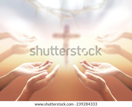 Human hands praying over blurred crown of thorns and Jesus on the cross over a sunset. - stock photo