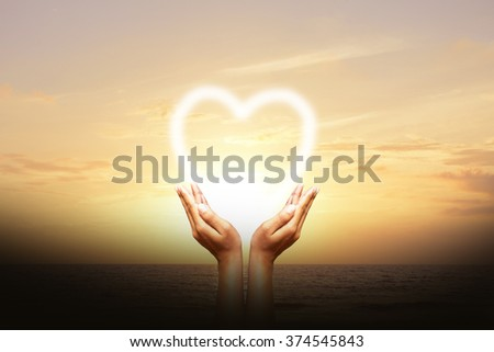 Human hands protect the heart Sky background - stock photo