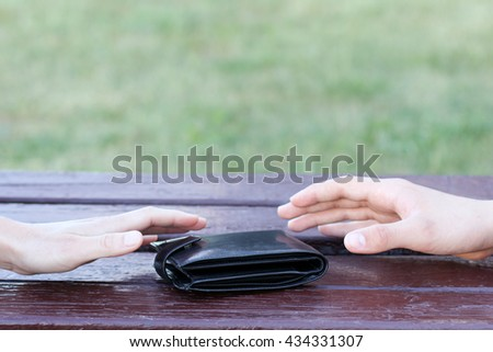 human hands reach for the black wallet lying on a bench / forgotten black purse - stock photo