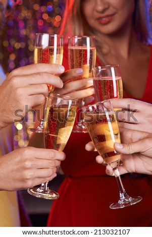 Human hands with champagne flutes toasting at party - stock photo