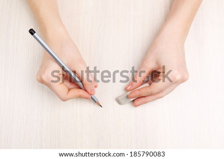 Human hands with pencil and erase rubber on wooden table background - stock photo