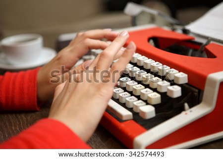 human hands writing on old red typewriter - stock photo