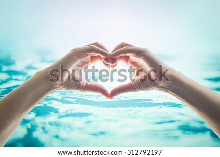 Human happy hands in heart shape showing love and friendship on blurred wavy clean blue turquoise color water background: CSR Saving world water and natural environment ocean concept/ campaign/ idea   - stock photo