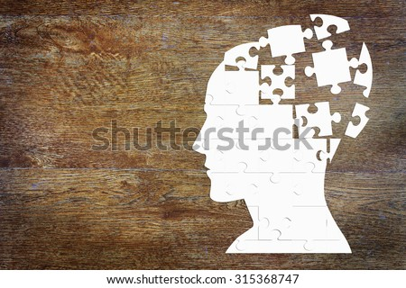 Human head as a set of puzzles on the wooden background - stock photo