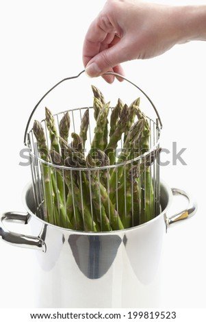 Human holding cooking pot with green asparagus - stock photo