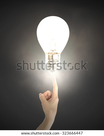 Human index finger pointing at lightbulb with bright light, on black background. - stock photo