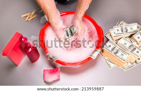 Human is washing dollars banknotes in foam - stock photo