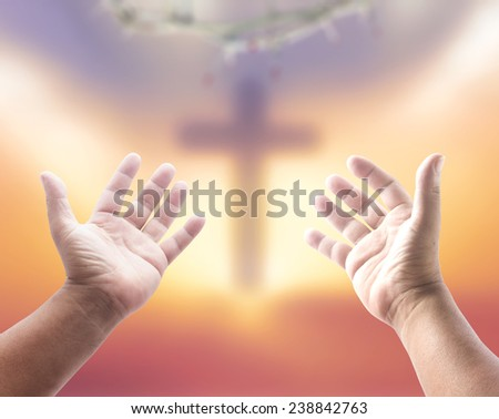 Human open empty hands with palms up, over blurred crown of thorns and the cross on a sunset. - stock photo