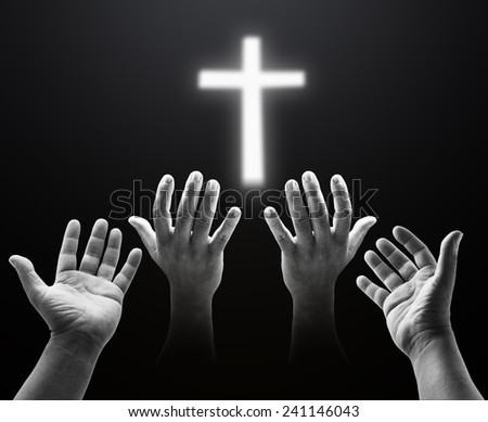 Human open empty hands with palms up over blurred the white cross. - stock photo