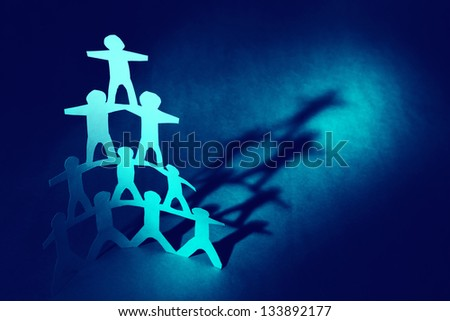 Human pyramid paper doll people - stock photo